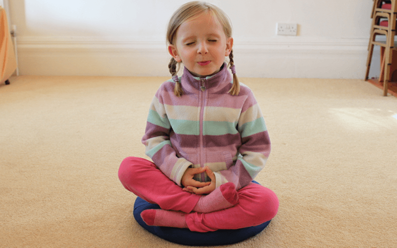 A child meditating with her hands in her lap