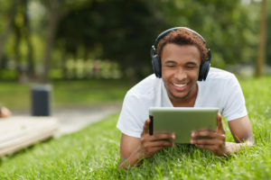 Young black man listening to meditation music on grass with headphones